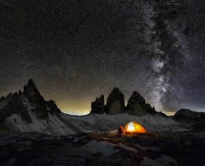 An illuminated tent in Dolomites under Milky Way at the Cime of the Dolomites (Drei Zinnen)
