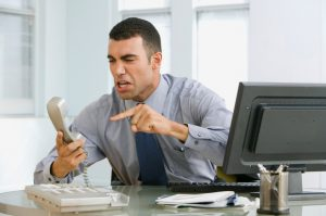 Hispanic businessman yelling at telephone
