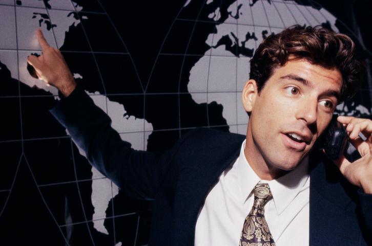 Businessman talking on a mobile phone while pointing to a world map